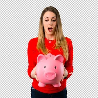 Surpresa jovem mulher loira segurando um piggybank