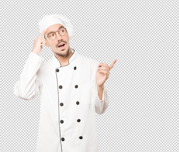 Surpreso jovem chef fazendo um gesto de concentração