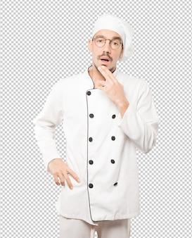 Surpreso jovem chef fazendo um gesto de dúvida