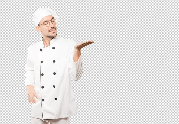Surpreso jovem chef segurando algo com a mão