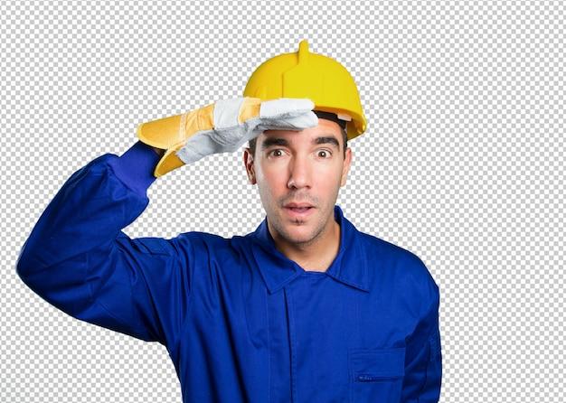 Surpreso trabalhador com gesto de busca no fundo branco