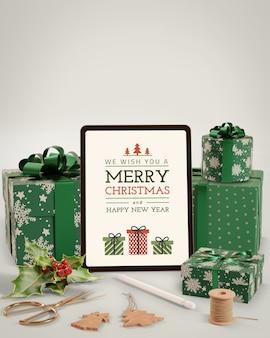 Tablet eletrônico ao lado de presentes para o natal