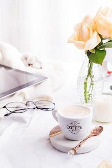 Tablet pc computador, xícara de café e rosas bege de manhã na cama branca