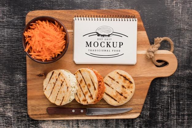 Tábua de madeira com faca e maquete de sanduíches orgânicos