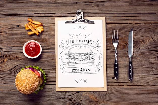 Talheres e hambúrguer com menu de batatas fritas no fundo de madeira