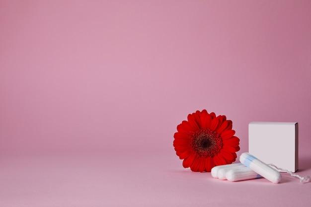 Tampões menstruais e flor vermelha isolados na tabela cor-de-rosa, vista superior. copie o espaço
