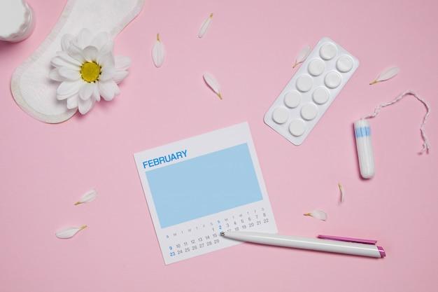 Tampões sanitários menstruais, almofadas e flor vermelha