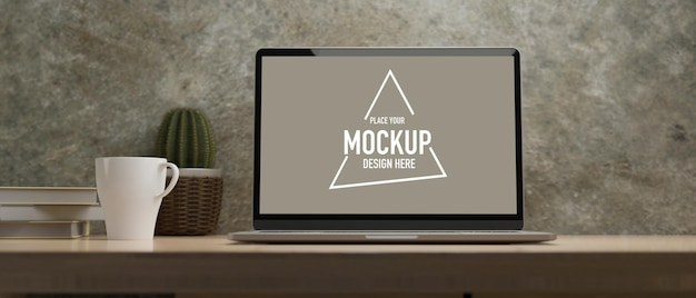 Tela do laptop para maquete na mesa de madeira com livros de cacto de café e sala de parede de concreto sob a luz