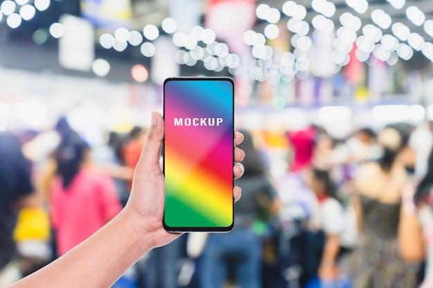 Telefone celular com turva multidão de pessoas na loja de compras