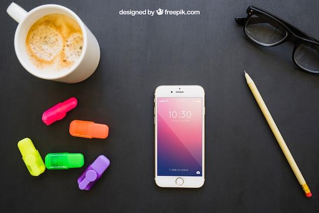 Telefone, marcadores, lápis, óculos e café