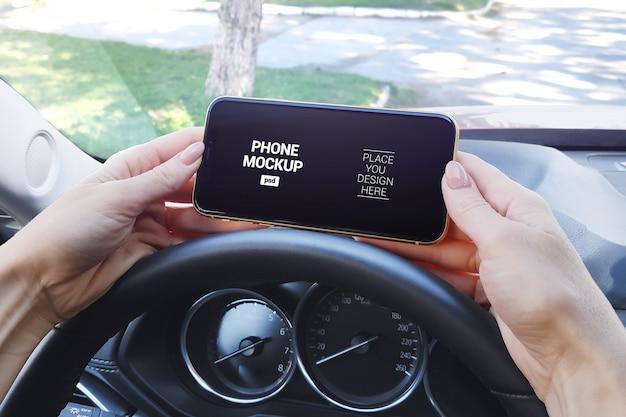 Telefone na mão da menina no volante de uma maquete de carro