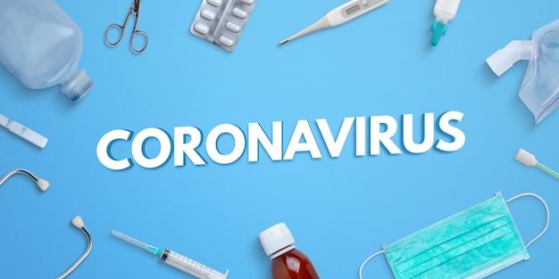 Texto de coronavírus na mesa azul cercada por equipamentos médicos e medicamentos. criador de cena do photoshop psd com camadas separadas