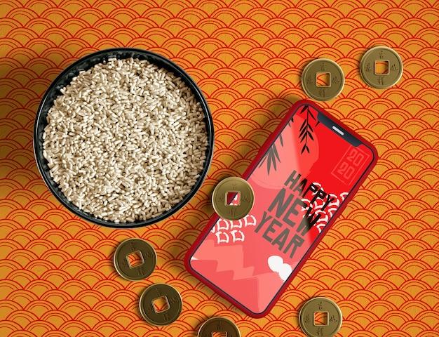 Tigela de vista superior de moedas de arroz dourado e maquete de telefone