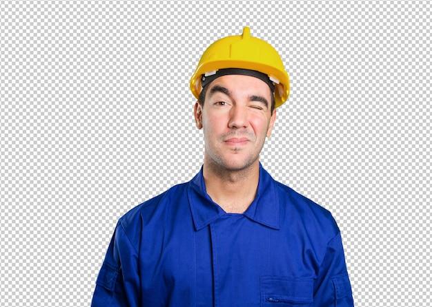 Trabalhador confiante, piscando um olho no fundo branco