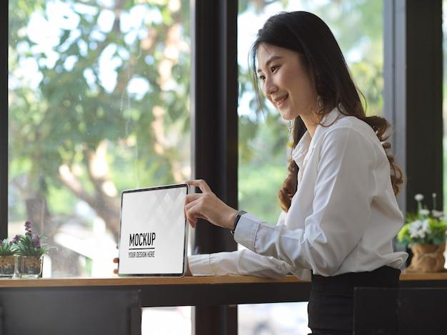 Trabalhador de escritório feminino apresentando maquete de tablet