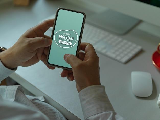 Trabalhador de escritório masculino enviando mensagens de texto em maquete de smartphone