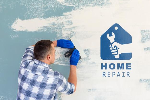 Trabalhador manual novo que limpa a tinta azul