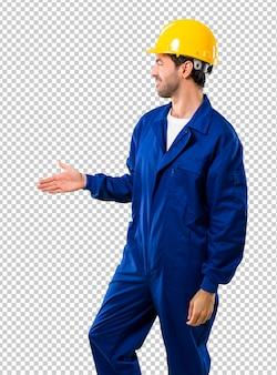 Trabalhador novo com aperto de mão do capacete após o bom negócio