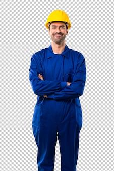 Trabalhador novo com o capacete que mantem os braços cruzados na posição frontal. expressão confiante