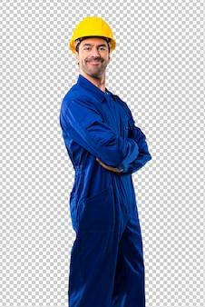 Trabalhador novo com o capacete que mantem os braços cruzados na posição lateral ao sorrir.