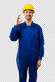 Trabalhador novo com o capacete que mostra um sinal aprovado com dedos. rosto de felicidade e satisfação