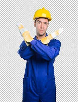Trabalhador sério, fazendo um gesto de proibição no fundo branco