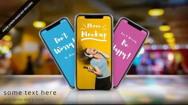 Três apple iphone x em uma superfície reflexiva com bokeh