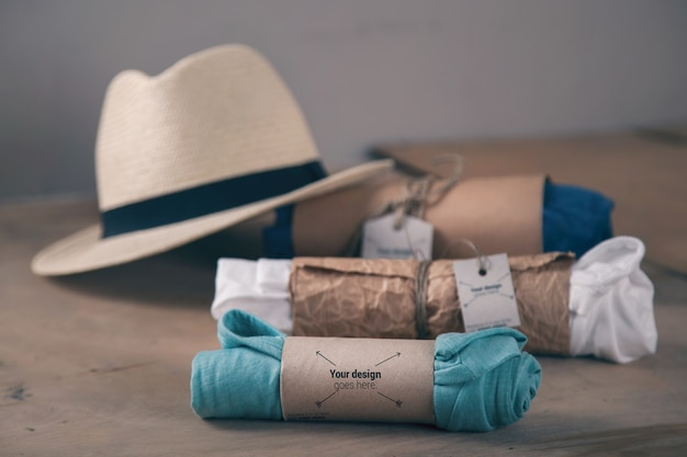 Três camisetas enroladas e maquete de chapéu