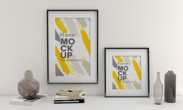 Um close de vasos ao lado de uma maquete de quadros em uma parede branca