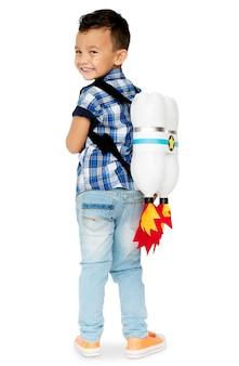 Um garotinho sorrindo usando um foguete de brinquedo nas costas sorrindo