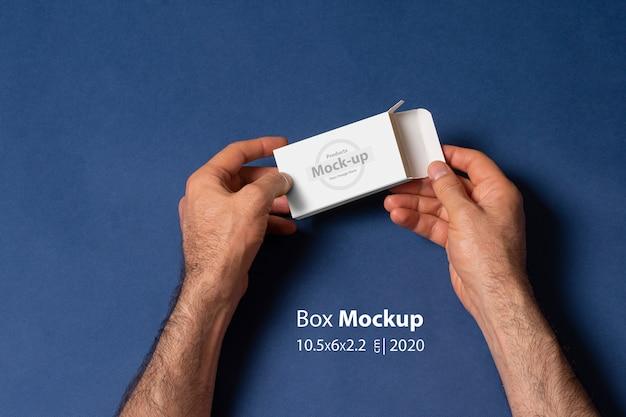 Um homem mãos abrindo uma caixa de comprimidos na frente da superfície azul escuro