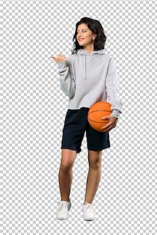 Um tiro de comprimento total de uma jovem mulher jogando basquete, apontando para o lado para apresentar um produto