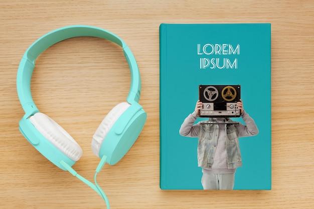 Variedade com mock-up de capa de livro e fones de ouvido