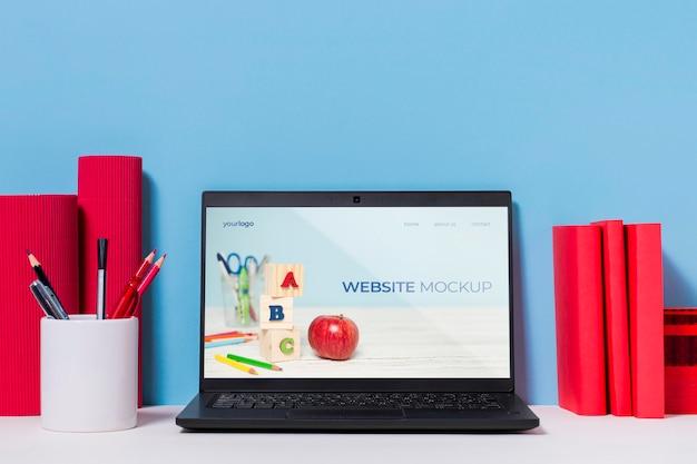 Variedade de canetas e laptop com mock-up