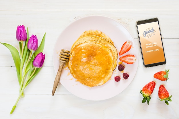 Variedade de panquecas de café da manhã ao lado do smartphone