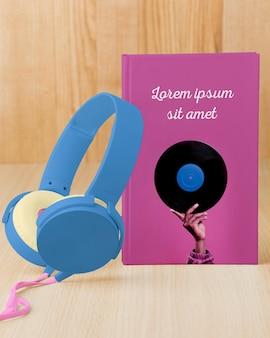 Variedade de vista frontal com maquete de capa de livro e fones de ouvido
