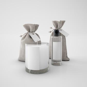Vela branca, sacos e frasco de perfume