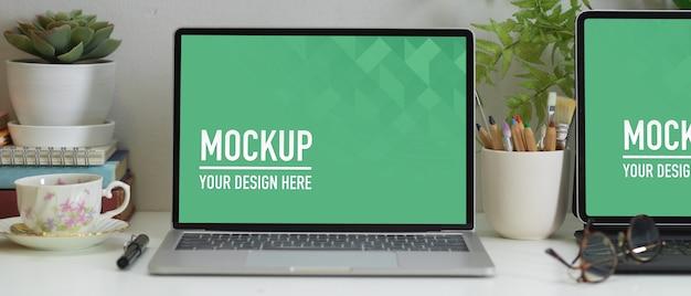 Visão aproximada da mesa de trabalho com laptop, tablet, suprimentos e decorações