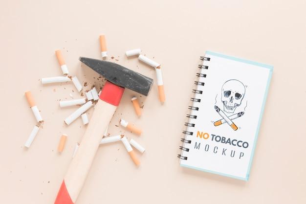 Visão superior de cigarros quebrados e martelo