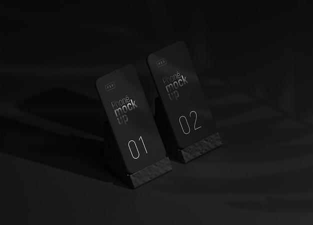 Vista em perspectiva da maquete da tela do aplicativo de smartphone com sobreposição de sombra e conjunto de suporte de telefone de dois dispositivos