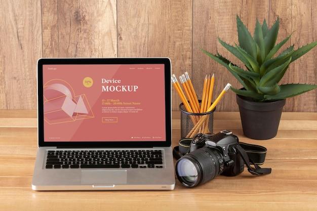 Vista frontal da área de trabalho de madeira do fotógrafo com laptop