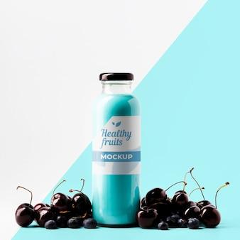 Vista frontal da garrafa de suco transparente com cerejas