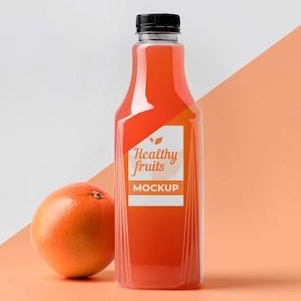 Vista frontal da garrafa de suco transparente com laranja