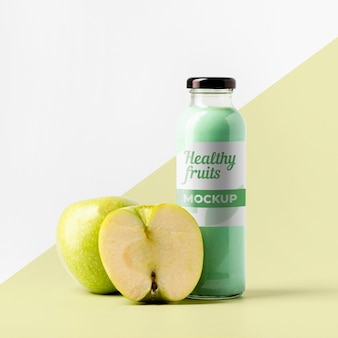 Vista frontal da garrafa de suco transparente com maçãs