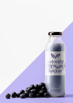 Vista frontal da garrafa de suco transparente com mirtilos