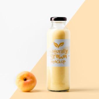 Vista frontal da garrafa de suco transparente com pêssego e tampa