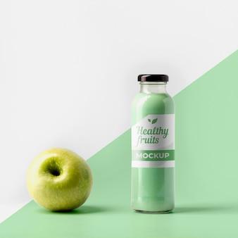 Vista frontal da garrafa de suco transparente com tampa e maçã