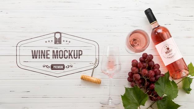 Vista frontal da garrafa de vinho rosa e uvas
