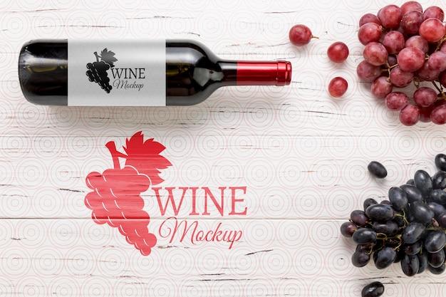 Vista frontal da garrafa de vinho tinto e uvas