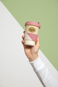 Vista frontal da mão segurando a xícara de café